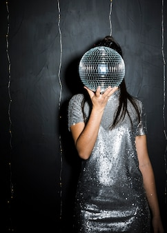 Woman closing face by disco ball