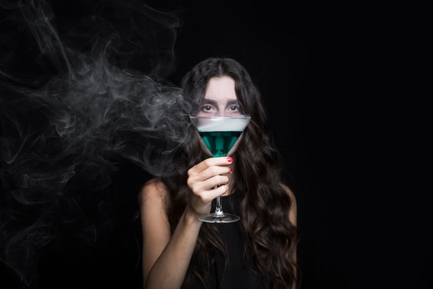 Woman closing face by goblet with smoking turquoise liquid