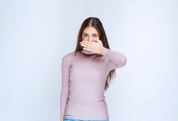 Женщина закрыла часть лица и глядя сквозь пальцы.