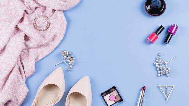 女性の服とアクセサリーのフラットは青いテーブルの上に置く
