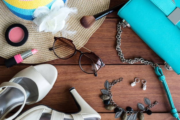 Woman clothes, makeup, and accessories on wooden background