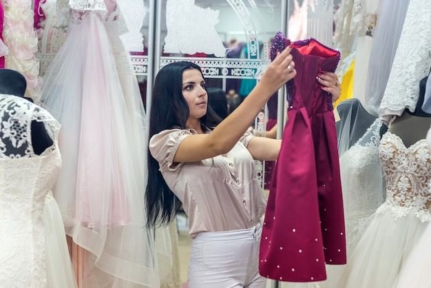Woman in clothes store chooses evening outfit