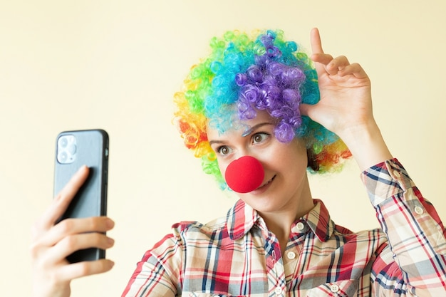 Woman in clown color wig taking selfie, funny fools day