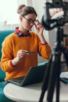 Женщина-тренер или психолог проводит онлайн-конференцию и записывает