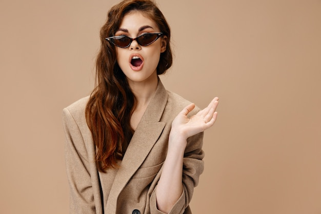 Woman in coat gesturing with hands glasses on face cropped view