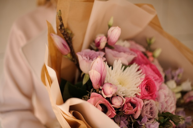 Woman in the coat holding a bouquet of tender color pink flowers