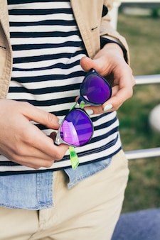 Woman in coat and striped t-shirt holding bright colored sunglasses