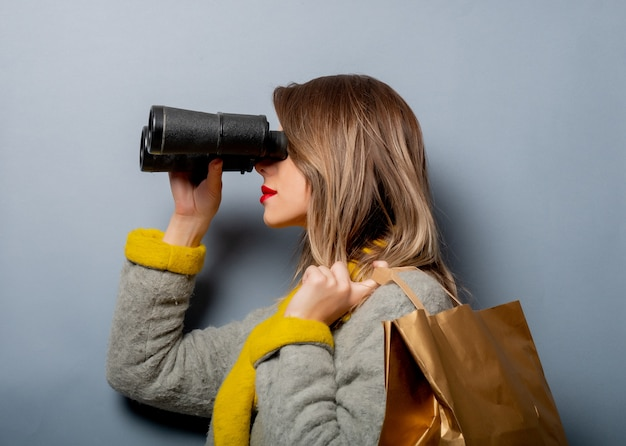 Woman in coat with shopping bag and binoculars