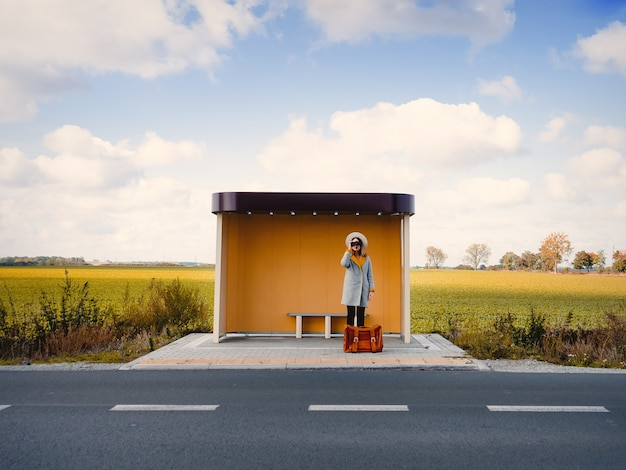 Woman in coat with suitcase and binocular on countryside bus stop