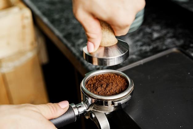 전문 커피 기계에 커피를 준비하는 여자 커피 숍 노동자를 닫습니다.