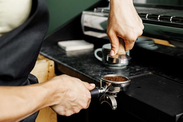 プロのコーヒーマシンでコーヒーを準備する女性のコーヒーショップの労働者