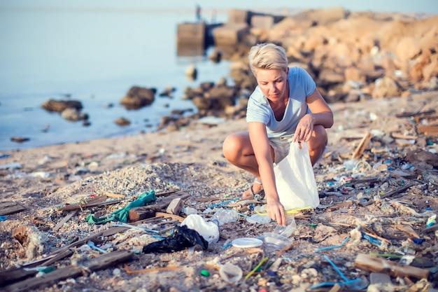 女性はビーチでゴミを収集します。環境保護のコンセプト
