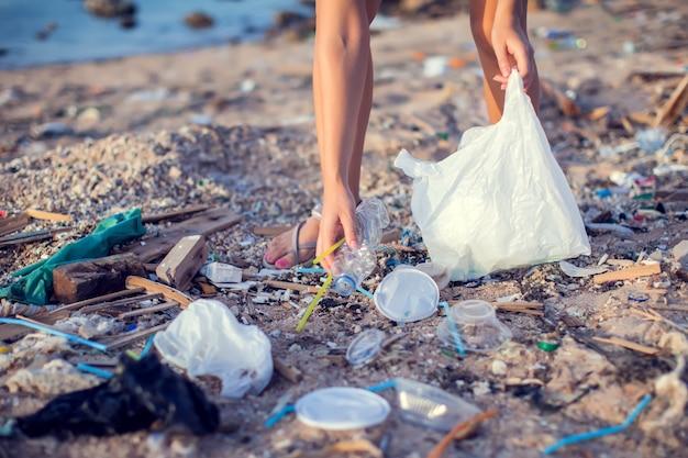 Женщина собирает мусор на пляже. концепция защиты окружающей среды