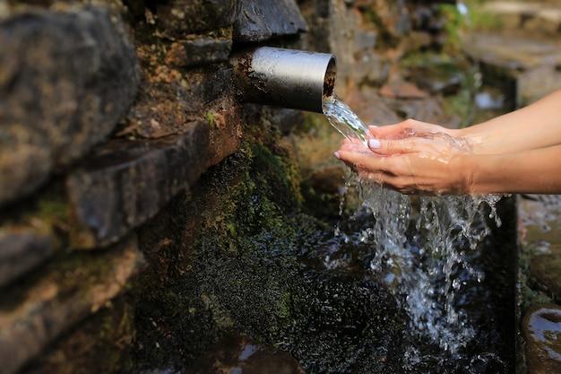Женщина собирает чистую воду в ладони руки из источника в стене, держит и пьет ее