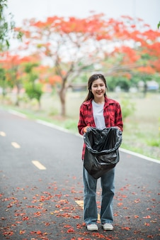 Woman collecting garbage in a black bag.