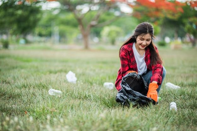 Женщина собирает мусор в черной сумке.