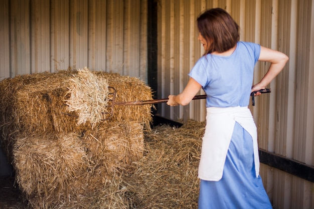 Woman collecting hay with pitchfork