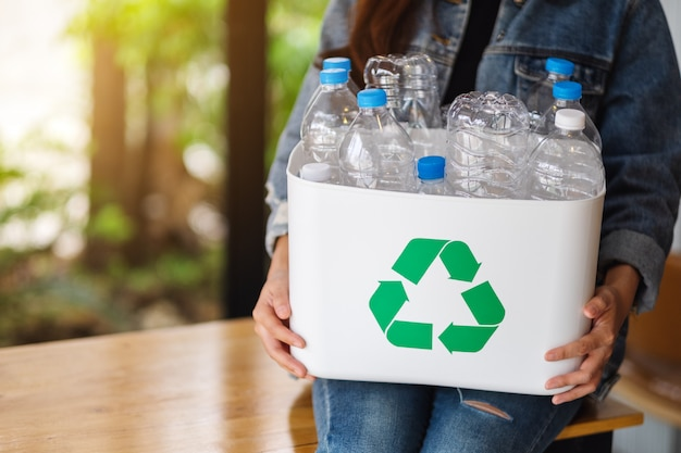 A woman collecting and holding a recyclable garbage plastic bottles into a trash bin at home