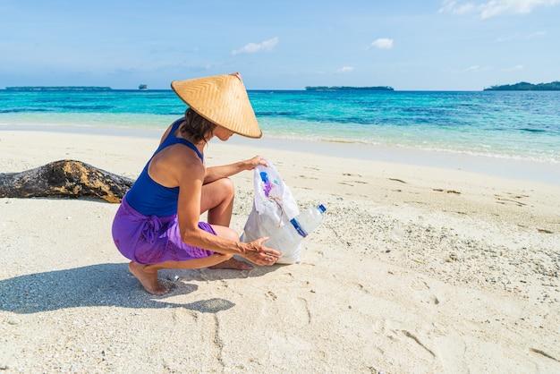 Женщина собирает пластиковые бутылки на красивом тропическом пляже, бирюзовое море, солнечный день, концепция утилизации мусора, охрана окружающей среды.