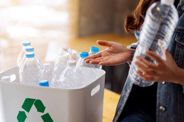 A woman collecting and separating recyclable garbage plastic bottles into a trash bin at home