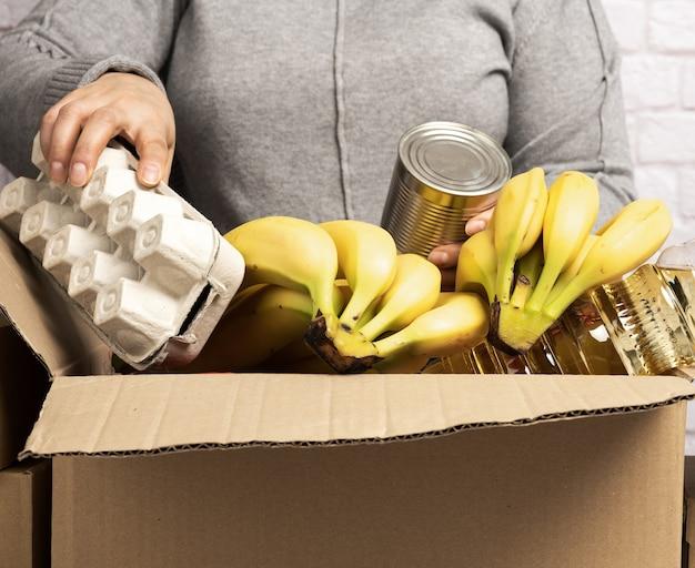 여성은 골판지 상자에 음식, 과일 및 물건을 모아 도움이 필요한 사람들을 돕고 자원 봉사 개념을 돕습니다. 제품 배송