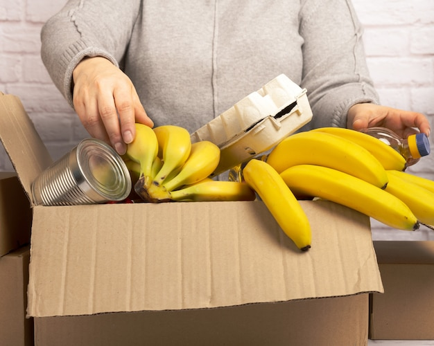 Woman collects food, fruits and things in a cardboard box to help those in need, help and volunteering concept. delivery of products