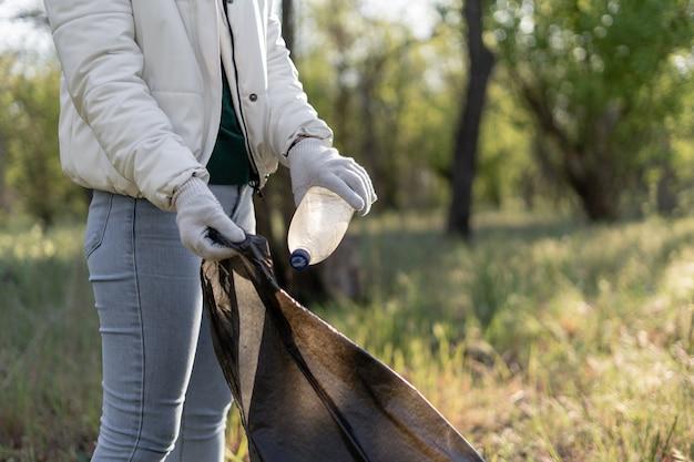Женщина собирает мусор в мешок. уборка парка от старых бутылок и пластика. девушка-волонтер помогает сделать мир чище.