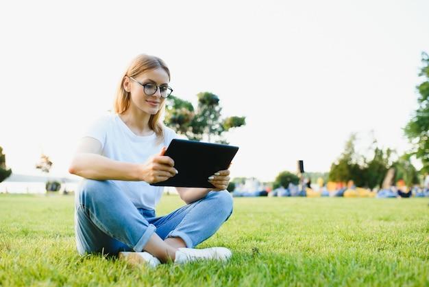 女子大生はタブレットpcを使用して草の上に座る