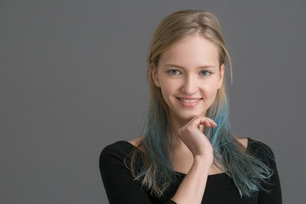 Женщина окрашивает волосы с синей прической и серой стеной. студийный снимок.