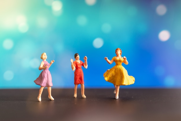 Woman in colored dress dancing against bokeh background