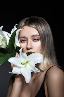 Woman colored hair color of a blonde with lily flower on black background. coloring hair woman model in ash color