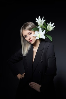 Woman colored hair color of a blonde with lily flower on black background.