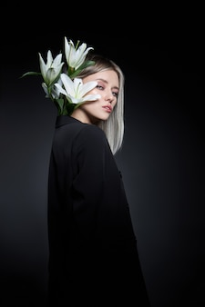 검은 배경에 백합 꽃과 금발의 여자 색 머리 색깔. 애쉬 컬러로 머리 여자 모델을 착 색. 여자의 초상화