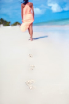 Woman in colorful dress walking on beach ocean leaving footprints in the sand