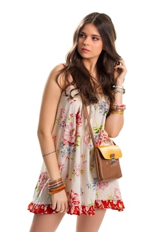 Woman in colorful floral dress. bicolor bag and short dress. stylish model wears casual clothes. quality leather purse with strap.