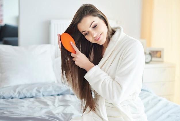 그녀의 긴 갈색 머리를 빗질하는 여자
