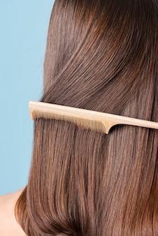 Женщина, расчесывающая гладкие волосы