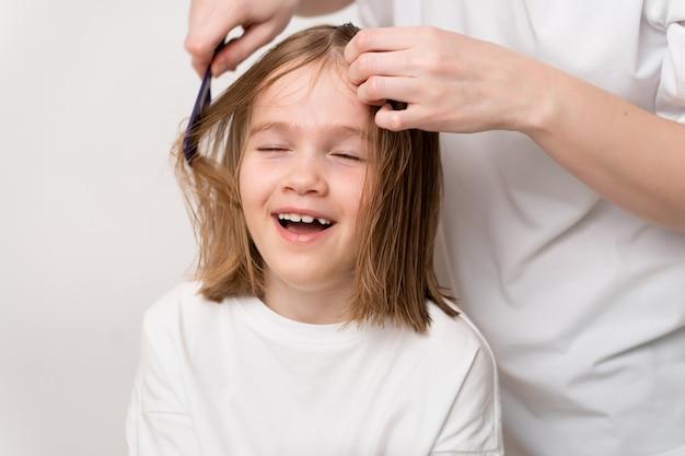 女性は、白い背景の上の面白い小さな女の子の髪をとかして行います。ママは美容師です。ビューティーサロンでお金を節約します。子供の髪のためのシャンプーと化粧品。