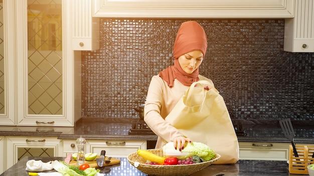 女性が鞄を持ってキッチンに来て商品を取り出す