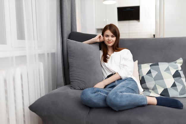 Woman in a comfortable apartment sits on the couch