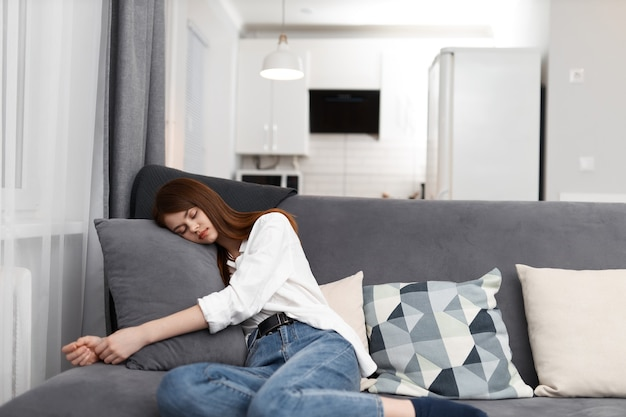 Woman comfortably settled down on the sofa in the apartment.
