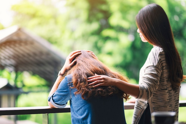 A woman comforting and giving encouragement to her sad friend
