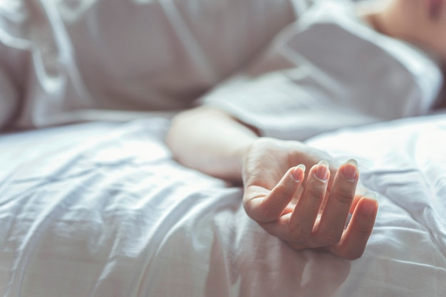 Woman committing suicide in bed focus on the hand of dead body the concept of die alone