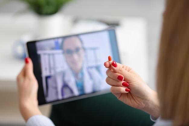 女性は、ビデオ通話の遠隔医療と投薬相談を介して医師とリモートで通信します