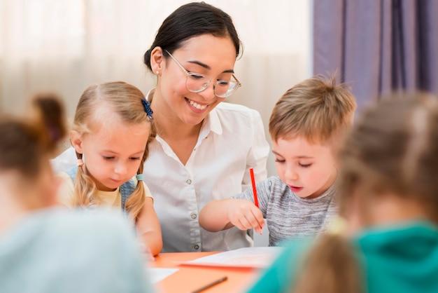 Женщина общается со своими учениками в классе
