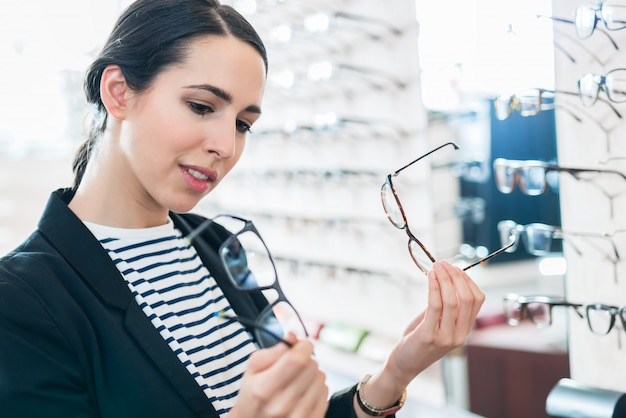Woman comparing glasses at optician