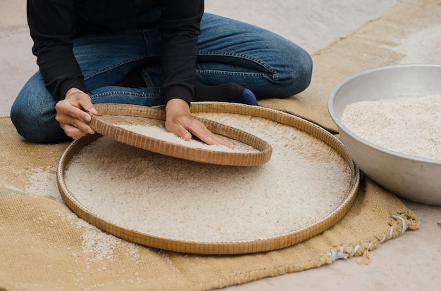 Woman competitive winnowing rice by using bamboo basketwork outdoor