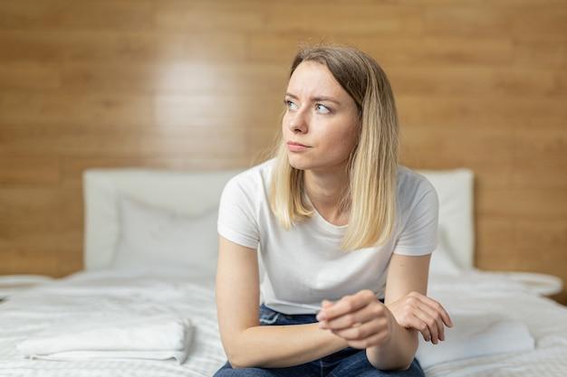 여자는 소파에 앉아 임신 테스트에 대해 불평