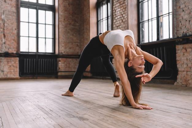 Woman do complex of stretching yoga asanas in loft style class. camatkarasana, wild thing