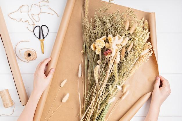 Женщина, составляющая букет из сухих цветов и трав, модное украшение интерьера, идея магазина ремесленников. вид сверху, плоская планировка